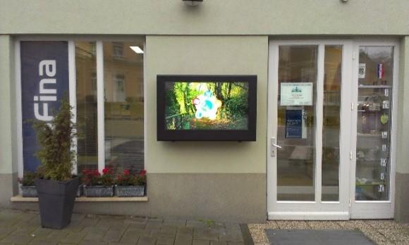 Point de vente qui utilise un panneau d'affichage extérieur avec écran tactile.